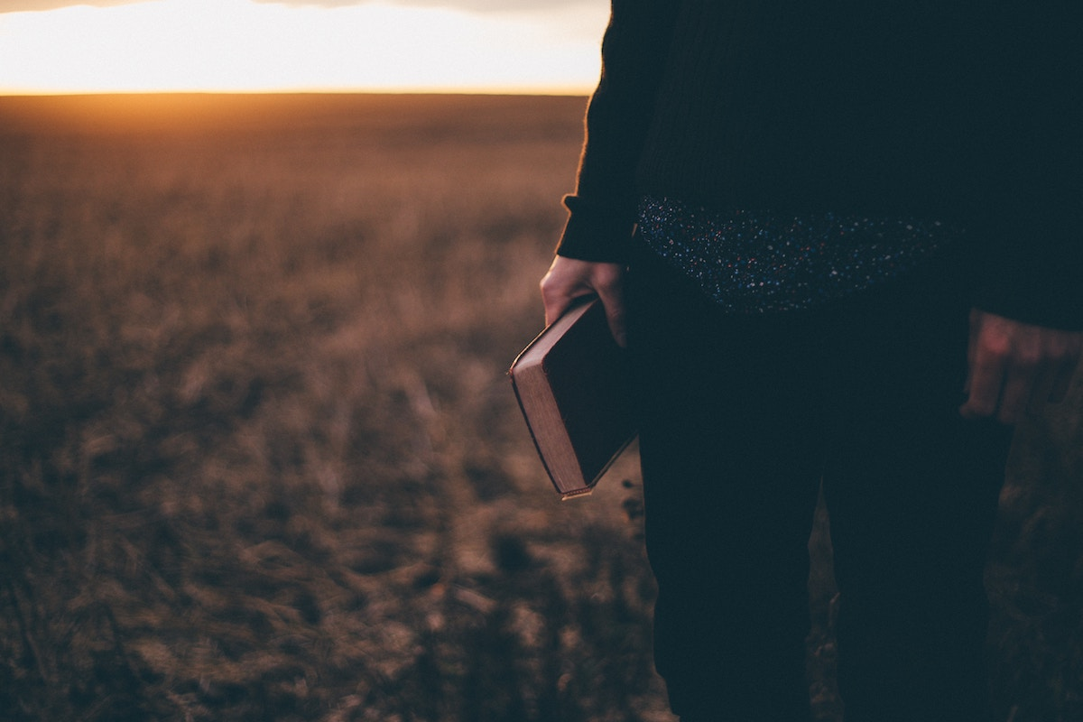 standing in field with book